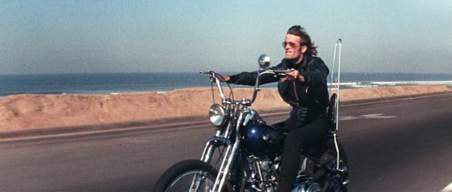 Peter Fonda fährt als Heavenly Blues mit seinem Motorrad auf einem Highway entlang der kalifornischen Küste.