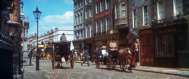 Pferdekutschen fahren durch eine Londoner Straße.