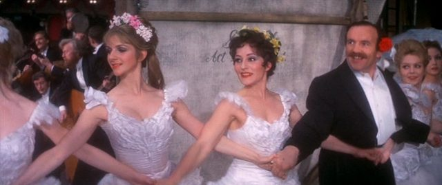 Dr. Watson (gespielt von Colin Blakely) tanzt mit russischen Ballerinas.