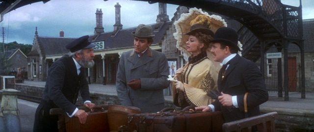 Sherlock Holmes, Gabrielle Valladon und Dr. Watson im Gespräch mit einem Bahnhofsmitarbeiter an einem Bahnsteig.
