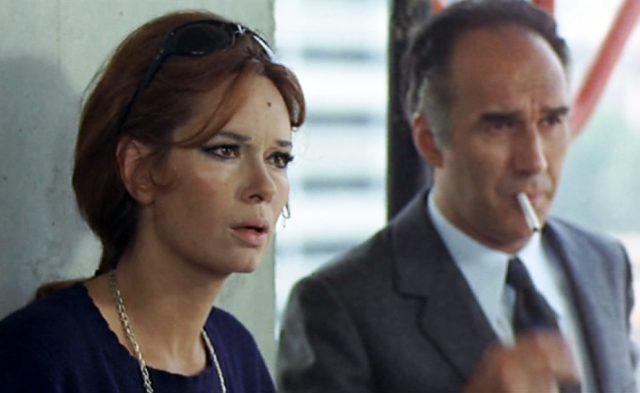Nahaufnahme von Catherine und Pierre Bérard; sie hat einen ungläubigen Blick und trägt eine Sonnebrille im Haar; er steht im Hintergrund mit Zigarette zwischen den Lippen.