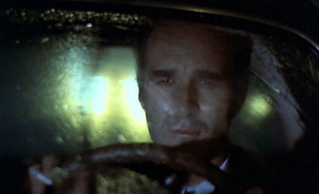 Nahaufnahme von Pierre Bérard mit nachdenklichem Blick hinter dem Steuer seines Fahrzeugs in nächtlicher Umgebung.