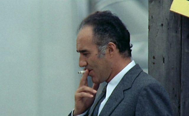 Pierre Bérard (gespielt von Michel Piccoli) beim Rauchen mit Zigarettenstummel.