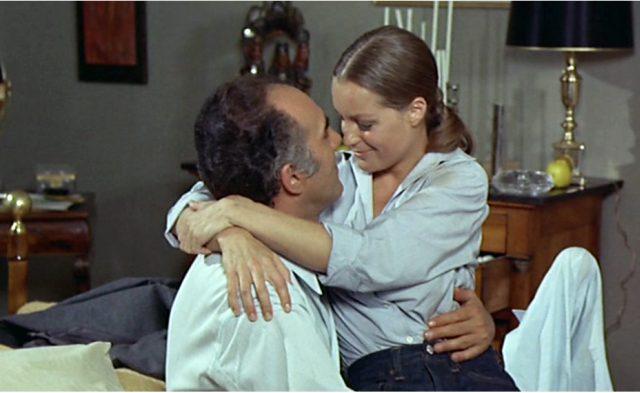 Pierre (gespielt von Michel Piccoli) sitzt in seinem Appartement und wird von Hélène (gespielt von Romy Schneider) umarmt.