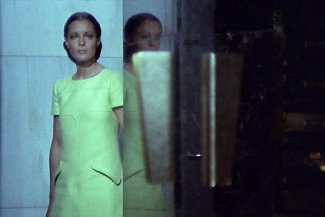 Hélène (gespielt von Romy Schneider) steht mit überlegendem Blick abends im Eingang eines Gebäudes.