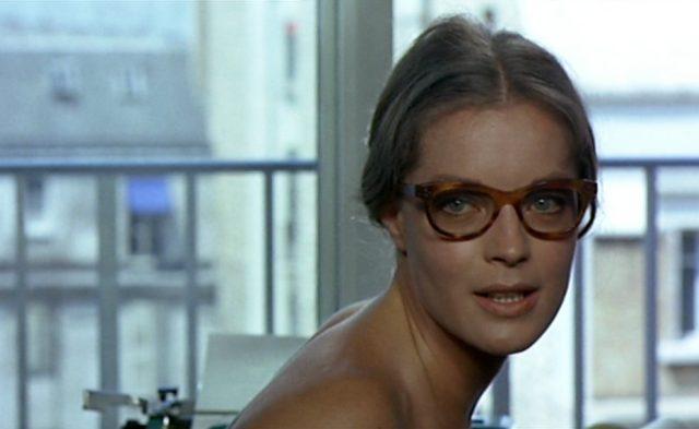 Nahaufnahme von Romy Schneider als Hélène mit stylisher Brille im Appartement.