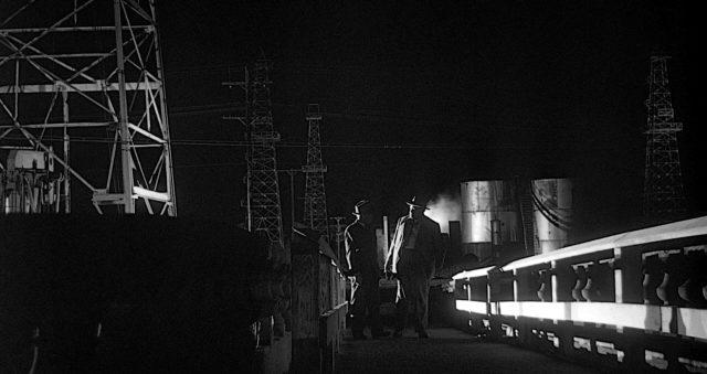 Düstere Szene, in der Quinlan und Menzies nachts auf einer kleinen Brücke im Vordergrund mehrerer Ölbohrtürme stehen.