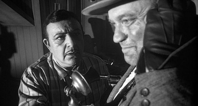 Hank Quinlan (gespielt von Orson Welles) telefoniert, während er Joe Grandi (gespielt von Akim Tamiroff) mit einem Revolver bedroht.
