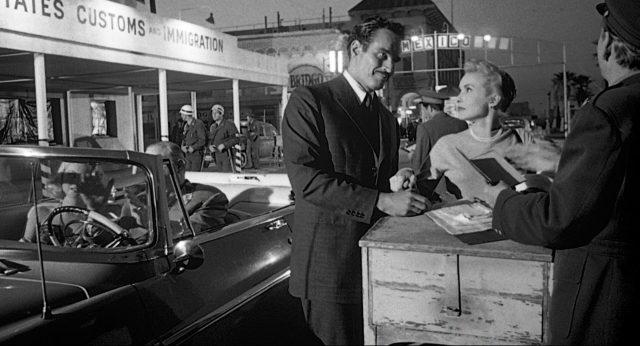 Das frischverheiratete Ehepaar Vargas (gespielt von Charlton Heston und Janet Leigh) am Grenzübergang; neben ihnen steht ein Cabriolet mit einem Mann und einer Frau als Insassen.