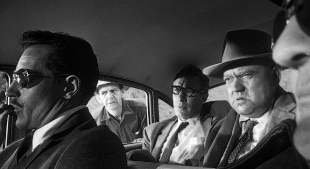 Mike Vargas (gespielt von Charlton Heston) mit Sonnebrille im Fahrzeug, in dem auch Quinlan (gespielt von Orson Welles) sitzt.