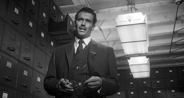 Mike Vargas (gespielt von Charlton Heston) steht im Archivkeller und hält seine Brille in den Händen.