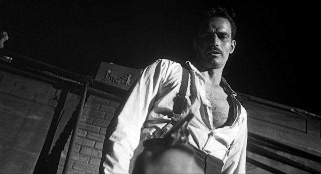 Charlton Heston als Mike Vargas mit offenem Hemd, der mit einer Waffe bedroht wird.