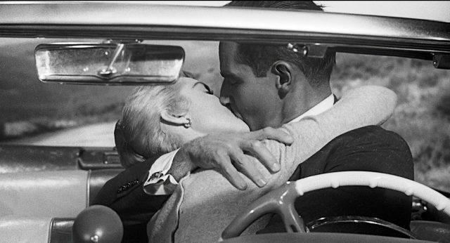 Susan und Mike Vargas (gespielt von Janet Leigh und Charlton Heston) küssen sich in ihrem Cabrio.