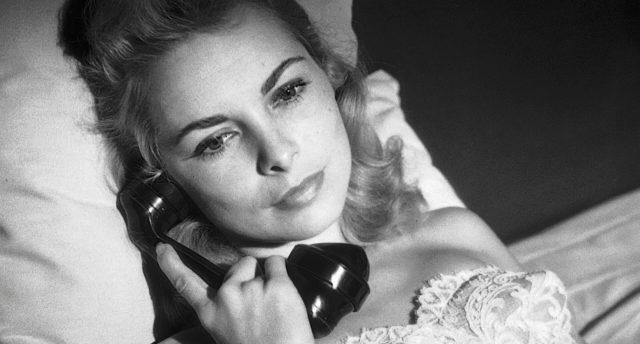 Nahaufnahme von Susan Vargas (gespielt von Janet Leigh) mit dem Telefonhörer am Ohr im Motel-Bett.