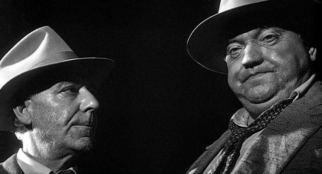 Nahaufnahme von Pete Menzies (gespielt von Joseph Calleia) und Hank Quinlan (gespielt von Orson Welles)  im Dunkeln.