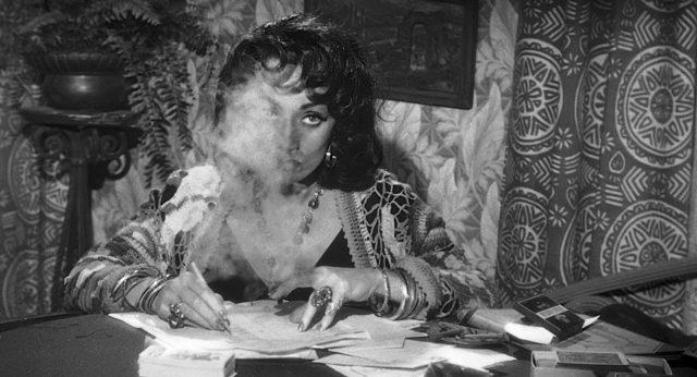 Marlene Dietrich als Bordellbetreiberin Tana, deren Gesicht durch den Zigarillo rauchverhüllt ist.
