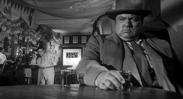 Hank Quinlan (gespielt von Orson Welles) sitzt am Tisch einer Bar und starrt nach schräg unten, seine rechte Hand umfasst ein Schnapsglas; im Hintergrund telefoniert Joe Grandi (gespielt von Akim Tamiroff).