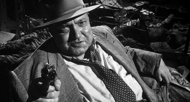 Hank Quinland (gespielt von Orson Welles) mit gezücktem Revolver.