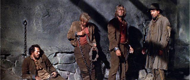Kriegsgefangene Südstaatler lehnen in düsterem Licht an einer schmutzigen Mauer.