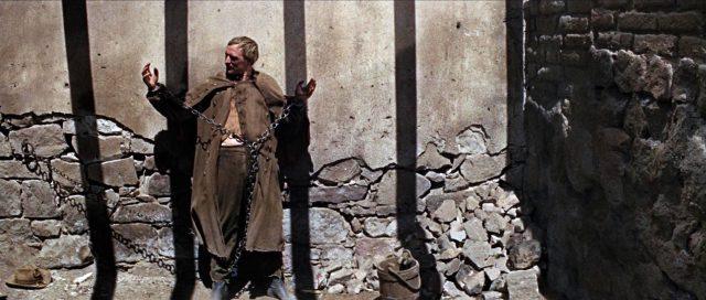 Tyreen vor einer Mauer in Ketten gelegt.