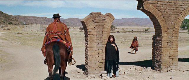 Ein Reiter zu Pferd neben einer Ruine, an der Senta Bergers Teresa Santiago lehnt.