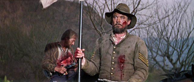 Ben Johnson als Kavallerist mit blutender Wunde zu Pferd.