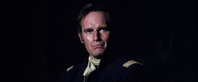 Nahaufnahme von Charlton Heston als Major Dundee vor dunklem Hintergrund.