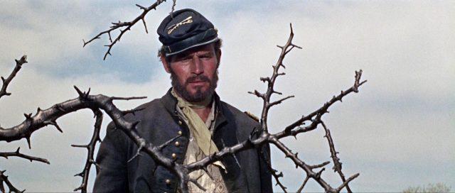 Nahaufnahme von Charlton Heston als Major Dundee in ramponierter Kleidung.