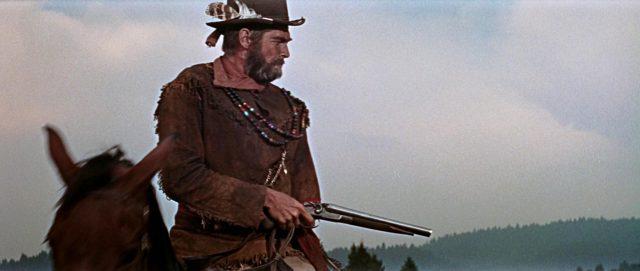 Nahaufnahme von James Coburn als Späher mit gezückter Pistole zu Pferd.