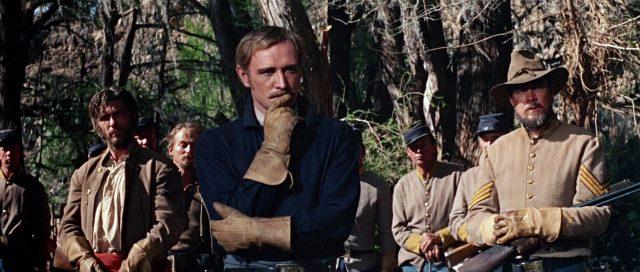 Captain Tyreen (gespielt von Richard Harris) in nachdenklicher Pose, im Hintergrund mit skeptischen Blicken seine Männer.
