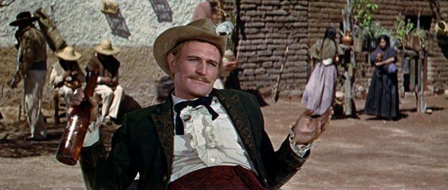 Captain Tyreen (gespielt von Richard Harris) sitzt mit einer Weinflasche im mexikanischen Dorf.