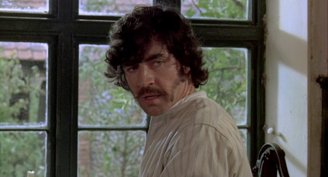 Naufnahme von Alan Bates als Ted Burgess vor einem Fenster seines Bauernhauses.