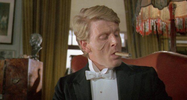Nahaufname von Trimingham (gespielt von Edward Fox) mit rauchender Zigarre.