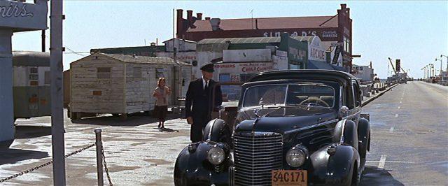 Eine dunkle Limousine parkt vor einem schäbigen Trailer an der Strandpromenade von Los Angeles.