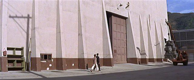 Clover und ein Studioangestellter laufen an dem riesigen Soundstage-Gebäude entlang.