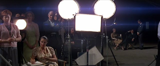 Blick auf vier unterschiedlich geformte Scheinwerfer und Crewmitglieder in einer dunklen Soundstage, im Hintergrund das Ehepaar Swan.