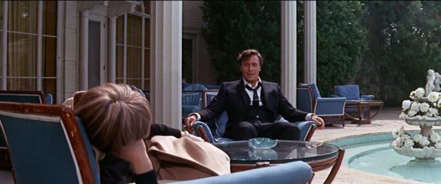 Studioboss Raymond Swan (gespielt von Christopher Plummer) sitzt in einem Gartensessel seines stattlichen Anwesens, im Vordergrund lehnt Daisy Clover mit dem Rücken zur Kamera in einem Stuhl.