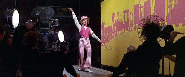 Daisy Clover (gespielt von Natalie Wood) im Kostüm beim Dreh einer Szene, im Vordergrund Mitglieder der Crew.