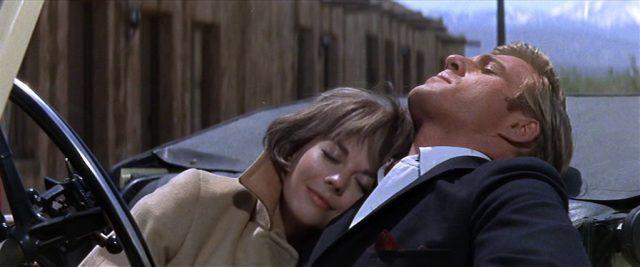 Daisy Clover (gespielt von Natalie Wood) und Wade Lewis (gespielt von Robert Redford) lehnen sich mit geschlossenen Augen im Cabrio vor einem Motel zurück., Copyright: Warner Bros., Park Place Prod.
