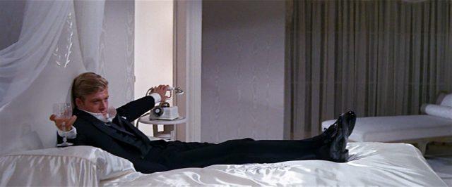 Wade Lewis (gespielt von Robert Redford) liegt mit ausgestreckten Beinen auf einem weißen Bett, in einer Hand hält er ein Glas.