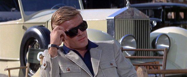 Wade Lewis (gespielt von Robert Redford) am Set mit Sonnenbrille, im Hintergrund parkt sein eleganter Cabrio., Copyright: Warner Bros., Park Place Prod.