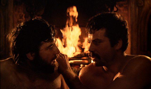 Nauaufnahme der nackten, zueinander gewandten Oberkörper von Rupert Birkin (gespielt von Alan Bates) und Gerald Crich (gespielt von Oliver Reed) vor dem lodernden Kaminfeuer.
