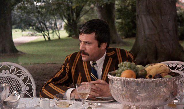 Gerald, gespielt von Oliver Reed, im gestreiften Jackett am Tisch, draußen im Park.