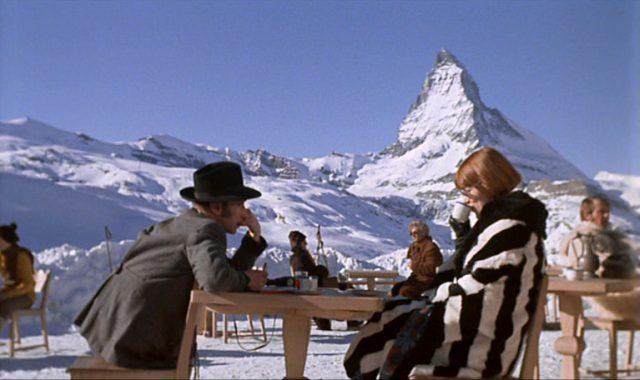 Loerke, gespielt von Vladek Sheybal, und Gudrun Brangwen sitzen vor alpinem Hintergrund an einem Holztisch.