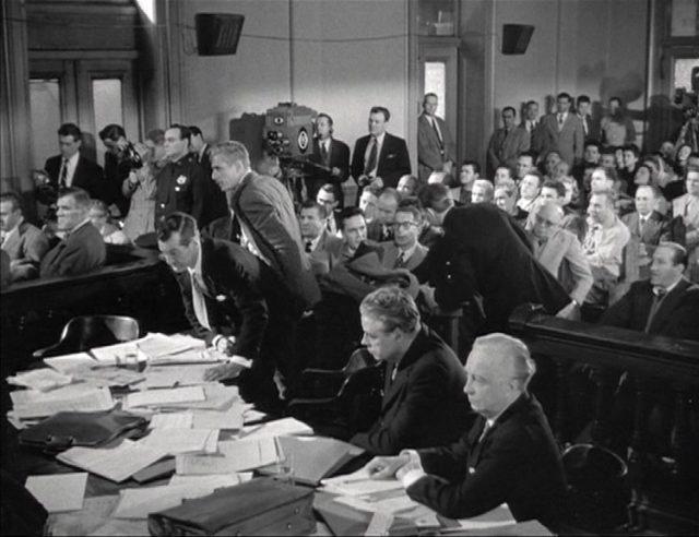 Gerichtsverhandlung, im Vordergrund ein von Papieren überfüllter Tisch.