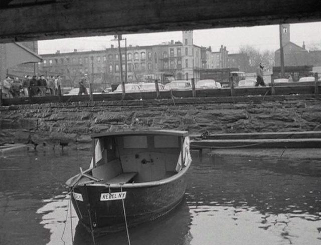 Hafenarbeiter laufen eine Straße nahe am Wasser entlang, im Vordergrund ankert ein kleines Boot.