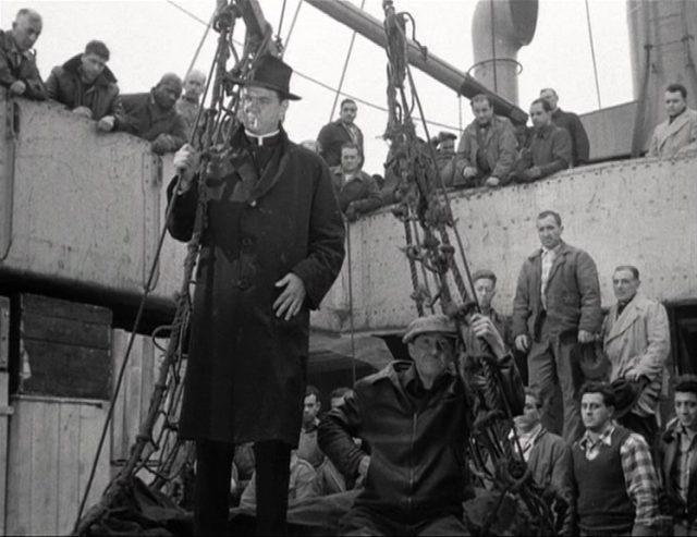 Pfarrer Barry (gespielt von Karl Malden) auf einer Lastenplattform auf einem Schiff, umgeben von Hafenarbeitern.