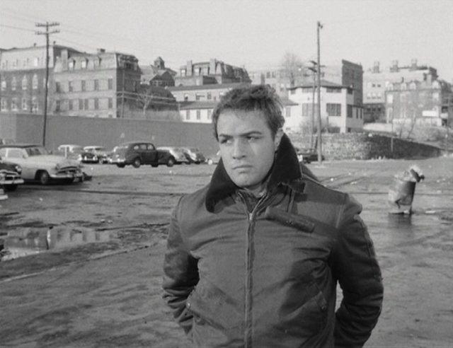 Marlon Brando als Terry Malloy, der mit misstrauischem Blick durch eine verregnete Straße wandelt.