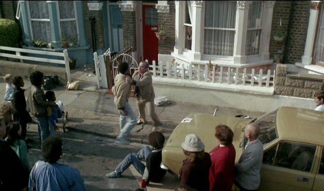 George in einer Prügelei vor einem Haus, der mehrere Passanten beiwohnen.
