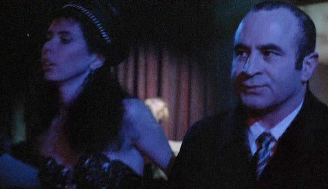 George mit ernsthaftem Gesicht in einem Erotiketablissement, nebem ihm eine Prostituierte.